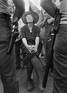 Dorothy Day on UFW picket line faces sheriff. When arthritis made standing difficult, Day confronted sheriffs from her portable three-legged golf stool. Lamont, California, August 1973.